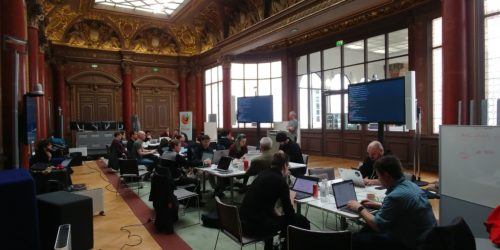 People clustered around 3 tables working on their computers in a gorgeous 19th century Parisian ballroom.