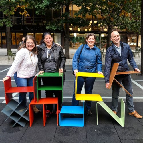 "Glenda Sims, Estelle Weyl, Janet Swisher and Adrian Roselli pose with metal letter-shaped chairs spelling ""HACK"" and ""MdN"""